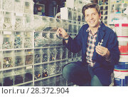 Купить «Male in hardware shop choosing bolts for repair», фото № 28372904, снято 4 мая 2017 г. (c) Яков Филимонов / Фотобанк Лори