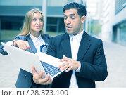Купить «Couple professionals are examinating project on laptop», фото № 28373100, снято 20 августа 2017 г. (c) Яков Филимонов / Фотобанк Лори