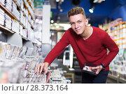 Купить «Man choosing movies on DVD», фото № 28373164, снято 15 февраля 2018 г. (c) Яков Филимонов / Фотобанк Лори