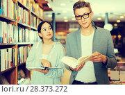 Купить «couple choosing and discussing literature», фото № 28373272, снято 18 января 2018 г. (c) Яков Филимонов / Фотобанк Лори