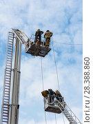Купить «Бойцы пожарной охраны в люльках на выдвижных лестницах», эксклюзивное фото № 28388860, снято 24 июня 2017 г. (c) Александр Щепин / Фотобанк Лори