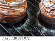 Купить «Cupcake pie crunch in the form of a roll sprinkled with powdered sugar on a dark background and an antique grille. Easter and Christmas baking. Top view, place for text, close-up», фото № 28389072, снято 8 апреля 2018 г. (c) Tetiana Chugunova / Фотобанк Лори