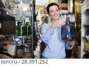 Купить «Portrait of positive woman choosing fragile glass item», фото № 28391252, снято 22 ноября 2017 г. (c) Яков Филимонов / Фотобанк Лори