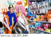 Купить «Positive couple trying on helmet with horns», фото № 28391444, снято 11 апреля 2017 г. (c) Яков Филимонов / Фотобанк Лори
