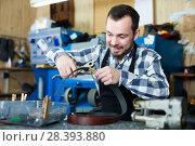 Купить «Male worker shaping new hole in belt», фото № 28393880, снято 2 февраля 2017 г. (c) Яков Филимонов / Фотобанк Лори