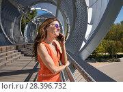 Купить «Woman with orange shirt in summer, at modern urban footbridge, talking on mobile, in Madrid city, Spain, Europe.», фото № 28396732, снято 14 сентября 2017 г. (c) easy Fotostock / Фотобанк Лори