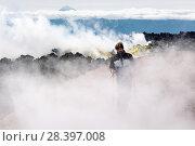 Купить «Турист идет в клубах пара и газа в кратере действующего вулкана», фото № 28397008, снято 7 августа 2014 г. (c) А. А. Пирагис / Фотобанк Лори
