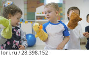 Купить «Children's developing a game room. Emotions of young children during entertaining classes. Kids will have fun playing with dolls that are put on the hand.», видеоролик № 28398152, снято 6 декабря 2019 г. (c) Константин Мерцалов / Фотобанк Лори