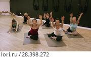 Купить «Smiling young women training yoga positions in modern yoga studio», видеоролик № 28398272, снято 14 февраля 2018 г. (c) Яков Филимонов / Фотобанк Лори