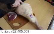 Мужчина с помощью ножа разделывает свиную ногу. Стоковое видео, видеограф Олег Хархан / Фотобанк Лори