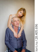 Купить «Portrait of Young Blonde Woman Undressing Her Senior Husband Sitting on the Chair on Wall Background. Couple with Age Difference», фото № 28405696, снято 9 октября 2017 г. (c) Ольга Балынская / Фотобанк Лори