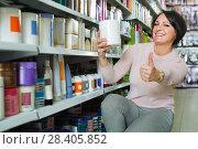 Купить «Pleasant woman choosing hair care products», фото № 28405852, снято 23 мая 2018 г. (c) Яков Филимонов / Фотобанк Лори