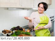 Купить «Middle age female in apron posing near kitchen top», фото № 28405880, снято 20 марта 2019 г. (c) Яков Филимонов / Фотобанк Лори