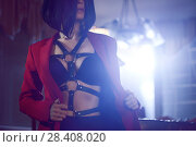 Купить «Artistic sensual portrait of a sexy young woman with short black hair taking off her red suit jacket revealing black bondage leather harness over her underwear in bright night light.», фото № 28408020, снято 5 марта 2018 г. (c) age Fotostock / Фотобанк Лори