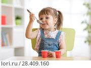 Купить «Funny child eating healthy food with a spoon at home», фото № 28409160, снято 18 августа 2019 г. (c) Оксана Кузьмина / Фотобанк Лори