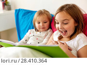 Купить «little girls or sisters reading book in bed», фото № 28410364, снято 15 октября 2017 г. (c) Syda Productions / Фотобанк Лори