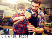 Купить «father and son with chisel working at workshop», фото № 28410504, снято 14 мая 2016 г. (c) Syda Productions / Фотобанк Лори