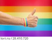 Купить «hand with gay pride rainbow wristband shows thumb», фото № 28410720, снято 2 ноября 2017 г. (c) Syda Productions / Фотобанк Лори