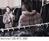 Купить «Young female customer examining new fur coat», фото № 28411180, снято 19 мая 2019 г. (c) Яков Филимонов / Фотобанк Лори