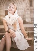 Купить «smiling woman sitting in the city center in shawl», фото № 28411548, снято 29 июля 2017 г. (c) Яков Филимонов / Фотобанк Лори