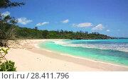 Купить «Small waves and white beach at Seychelles islands. La Digue, Anse Cocos», видеоролик № 28411796, снято 14 мая 2018 г. (c) Mikhail Starodubov / Фотобанк Лори