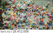 Купить «Цветные кусочки пластика смываются водой», видеоролик № 28412008, снято 15 мая 2018 г. (c) FMRU / Фотобанк Лори
