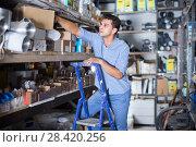 Купить «foreman is standing on the stairs near the shelves with boxes», фото № 28420256, снято 26 июля 2017 г. (c) Яков Филимонов / Фотобанк Лори