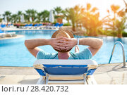 Купить «Relax in the pool summer. Young and successful man lying on a sun lounger at the hotel on the background of sunset, concept time to travel», фото № 28420732, снято 19 апреля 2018 г. (c) Happy Letters / Фотобанк Лори