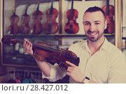 Купить «Male musician selecting violin», фото № 28427012, снято 19 января 2019 г. (c) Яков Филимонов / Фотобанк Лори