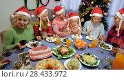 Купить «Happy family is talking at the table in time celebration New Year at home.», видеоролик № 28433972, снято 17 января 2018 г. (c) Яков Филимонов / Фотобанк Лори