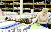 Купить «Portrait of an attractive girl choosing fabric among the variety on the shelves in the store», видеоролик № 28433976, снято 28 марта 2018 г. (c) Яков Филимонов / Фотобанк Лори