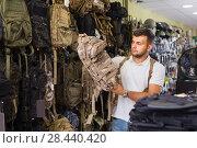 Купить «Man choosing textile backpack gun in military shop», фото № 28440420, снято 4 июля 2017 г. (c) Яков Филимонов / Фотобанк Лори