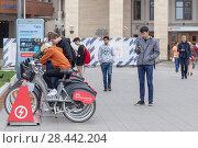 Купить «Молодые люди берут напрокат электрический велосипед на станции проката электровелосипедов. Москва, Россия», фото № 28442204, снято 19 мая 2018 г. (c) Ольга Шуклина / Фотобанк Лори