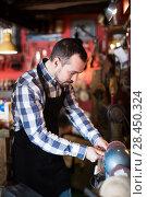 Купить «Young man worker energetically working in leather workshop», фото № 28450324, снято 15 августа 2018 г. (c) Яков Филимонов / Фотобанк Лори
