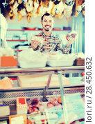 Купить «Smiling male seller showing sorts of meat», фото № 28450632, снято 2 января 2017 г. (c) Яков Филимонов / Фотобанк Лори