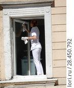 Купить «Женщина протирает окно со стороны улицы в офисном помещении нежилого дома. Улица Красная Пресня, 30, строение 1. Пресненский район. Москва», эксклюзивное фото № 28450792, снято 9 мая 2018 г. (c) lana1501 / Фотобанк Лори