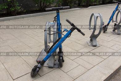 Купить «Электросамокаты сервиса YouDrive lite, привязанные к велосипедной стойке», фото № 28451456, снято 22 мая 2018 г. (c) Дмитрий Рыженков / Фотобанк Лори
