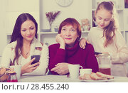 Купить «Bored grandma with daughter and granddaughter looking at phones», фото № 28455240, снято 25 ноября 2017 г. (c) Яков Филимонов / Фотобанк Лори