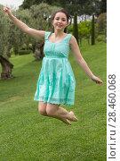Купить «positive young brunette girl in dress jumping at the garden», фото № 28460068, снято 18 апреля 2017 г. (c) Яков Филимонов / Фотобанк Лори