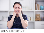 Купить «Positive brown-eyed girl at table», фото № 28460124, снято 9 апреля 2017 г. (c) Яков Филимонов / Фотобанк Лори
