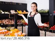 Купить «Woman assistant displaying fruits of grocery shop», фото № 28460316, снято 23 ноября 2016 г. (c) Яков Филимонов / Фотобанк Лори