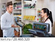Купить «Shopping assistant helping customer to weigh cabbage», фото № 28460320, снято 23 ноября 2016 г. (c) Яков Филимонов / Фотобанк Лори
