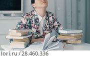 Купить «Woman is tired of studying books», видеоролик № 28460336, снято 28 марта 2018 г. (c) Илья Шаматура / Фотобанк Лори