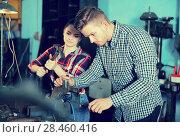 Купить «Two happy masters are standing with tools», фото № 28460416, снято 10 октября 2017 г. (c) Яков Филимонов / Фотобанк Лори