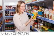 Купить «Cheerful female customer choosing pickle goods in the store», фото № 28467796, снято 11 апреля 2018 г. (c) Яков Филимонов / Фотобанк Лори