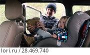 Купить «Father puts on toddler boot in car interior», видеоролик № 28469740, снято 28 мая 2018 г. (c) Ekaterina Demidova / Фотобанк Лори