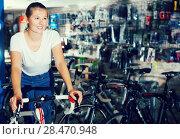 Купить «Young woman is standing with bicycle», фото № 28470948, снято 13 сентября 2017 г. (c) Яков Филимонов / Фотобанк Лори