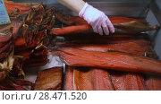 Купить «Женская рука продавца выбирает копченую красную рыбу в витрине магазина», видеоролик № 28471520, снято 20 мая 2018 г. (c) А. А. Пирагис / Фотобанк Лори