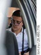 Купить «Business man on back seat of car puts on glasses», фото № 28480716, снято 20 июля 2014 г. (c) Ingram Publishing / Фотобанк Лори