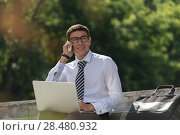 Man with laptop calling by phone at summer park on bright day. Стоковое фото, фотограф Kirill Kedrinskiy / Ingram Publishing / Фотобанк Лори